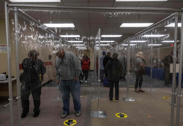 Residents of Lucas County, Ohio, line up behind plastic barriers and stand nearly two meters apart to avoid contamination.