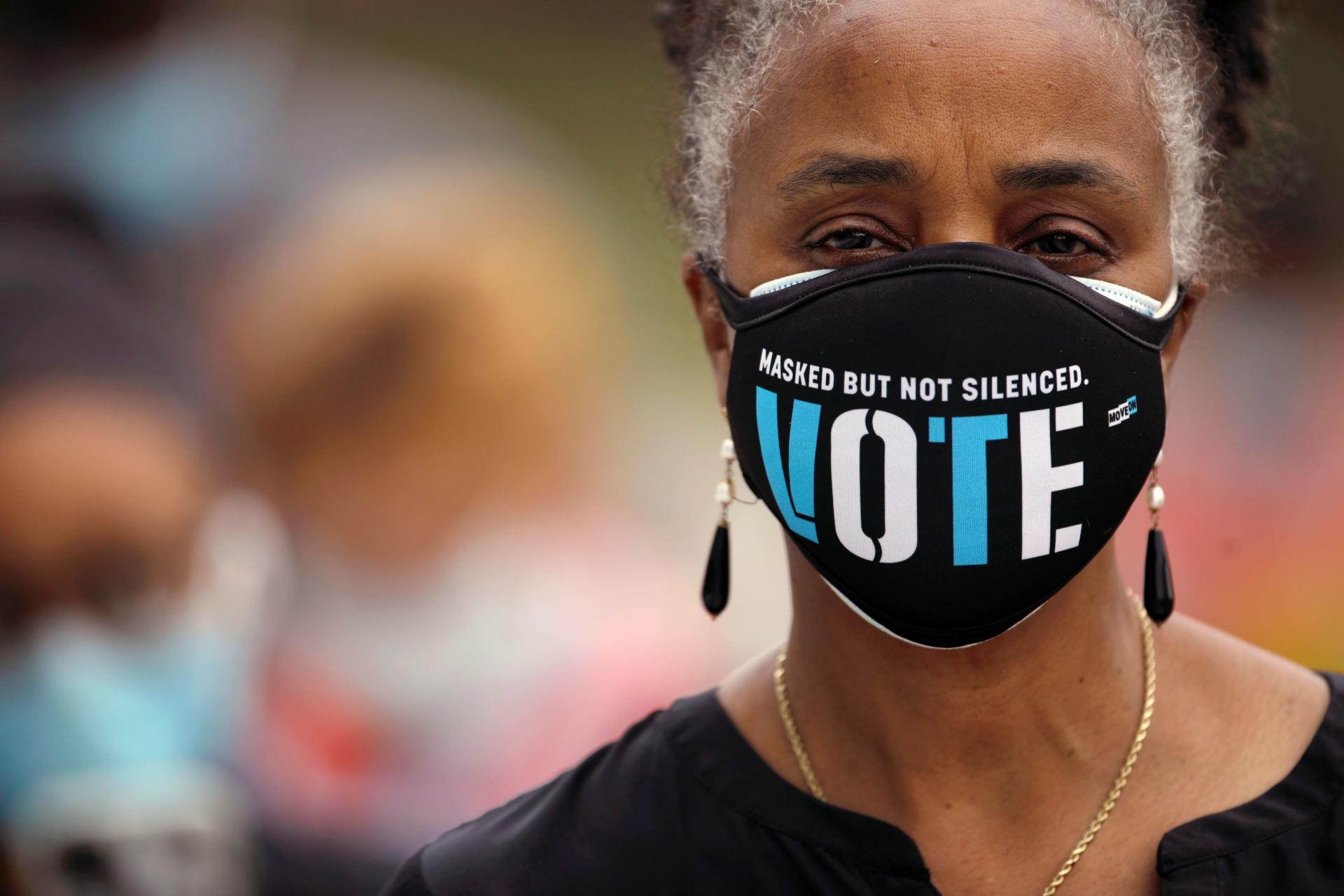 A woman wears a mask with a message urging voter turnout as she lines up to vote on October 15, the first day of the snap elections, in Durham, North Carolina.
