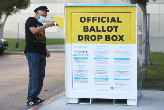 On October 14, a pedestrian casts his mail-in ballot at an official ballot box outside an office in Norwalk, California.