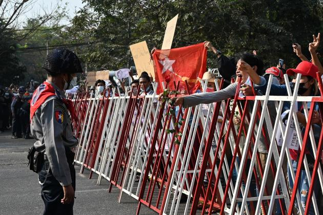 Protesters hand roses to riot police in Yangon on February 7.