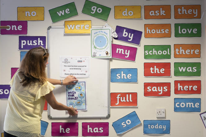 A teacher places signs in a classroom on the transmission of Covid-19 at Lostock Hall Primary School in Poynton near Manchester, England on Wednesday May 20, 2020.