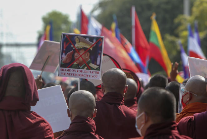 Buddhist monks show a disfigured image of the Burmese army commander-in-chief General Min Aung Hlaing during a street march against the military coup in Mandalay, Burma, Friday February 12, 2021.