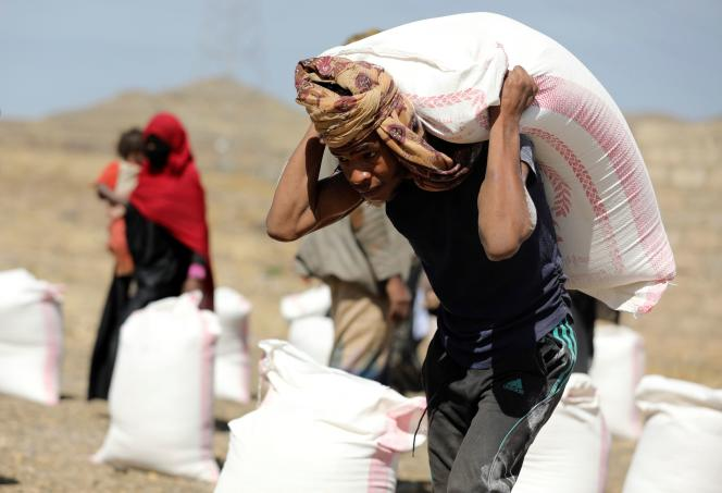 A worker carries a bag of flour provided by an NGO to beneficiaries of a camp for internally displaced people in the suburbs of Sanaa, Yemen, on March 1, 2021.