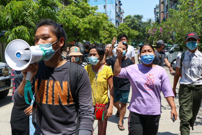 Young demonstrators make the sign of resistance with three fingers during a march in Rangoon, Saturday, April 10, 2021.
