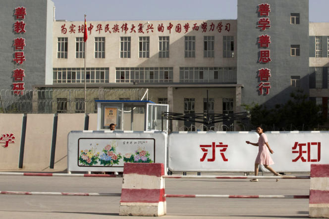 On August 31, 2018, a woman walks past a building billed as a school in Kashgar Prefecture, Xinjiang, western China.  Beijing said it had sentenced two former officials in the region, including the former head of the education department, to death on charges of separatism and corruption.
