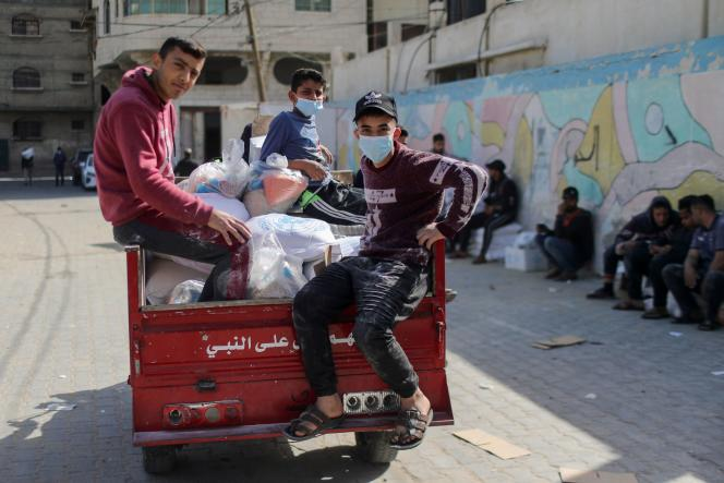 Palestinian youths take food they received from a United Nations-run aid distribution center in Gaza on April 7.