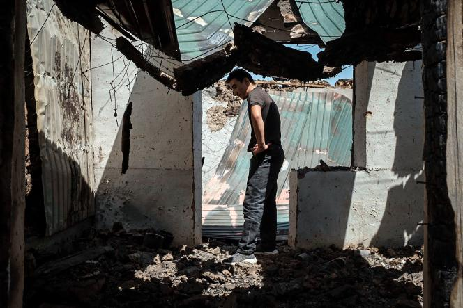 A man, amid the ruins of his burnt down business, in Maksat, Kyrgyzstan, on the border with Tajikistan, May 2, 2021.