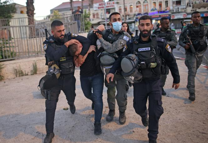 Israeli police forces arrest a Palestinian near the Damascus Gate in East Jerusalem as ultra-nationalists participate in the flag march near the Old City of Jerusalem on June 15, 2021.