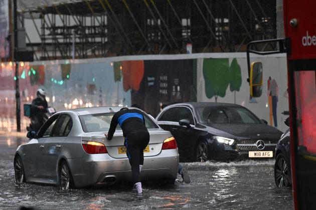 A driver forced to push his car on a flooded London street in the Nine Elms district on July 25, 2021.