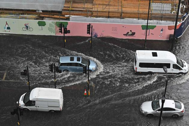 Cars drive through a flooded London street in the Nine Elms district on July 25, 2021.