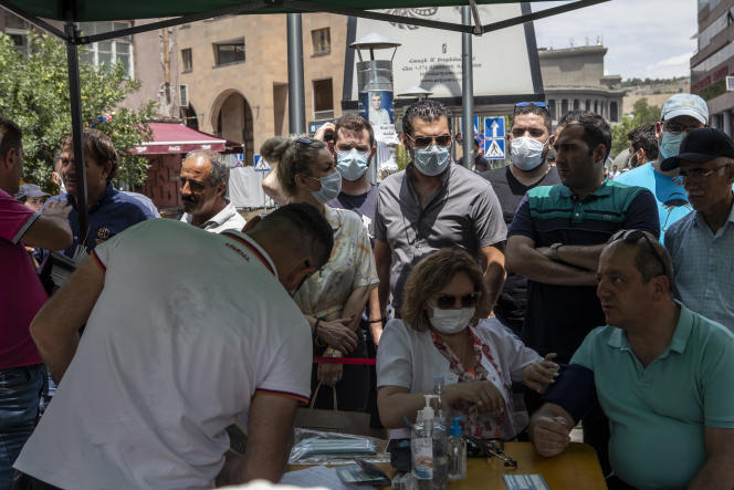 Iranians wait to be vaccinated outside a mobile clinic in Yerevan, Armenia, July 7, 2021.