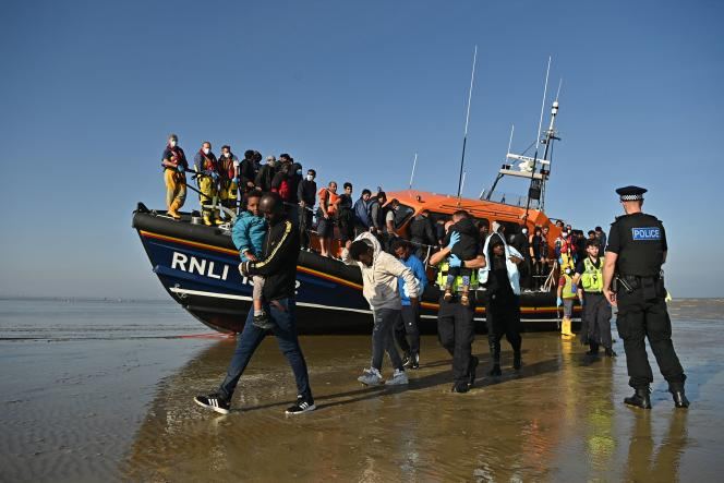Migrants are escorted by a rescue team from the Royal National Lifeboat Institution in Dungeness, England on September 7, 2021.